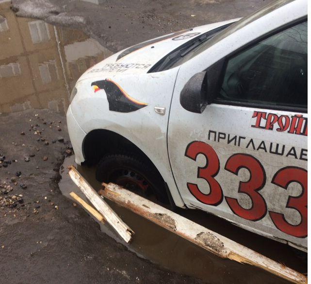 В ярославском дворе автомобиль такси застрял в дорожной яме
