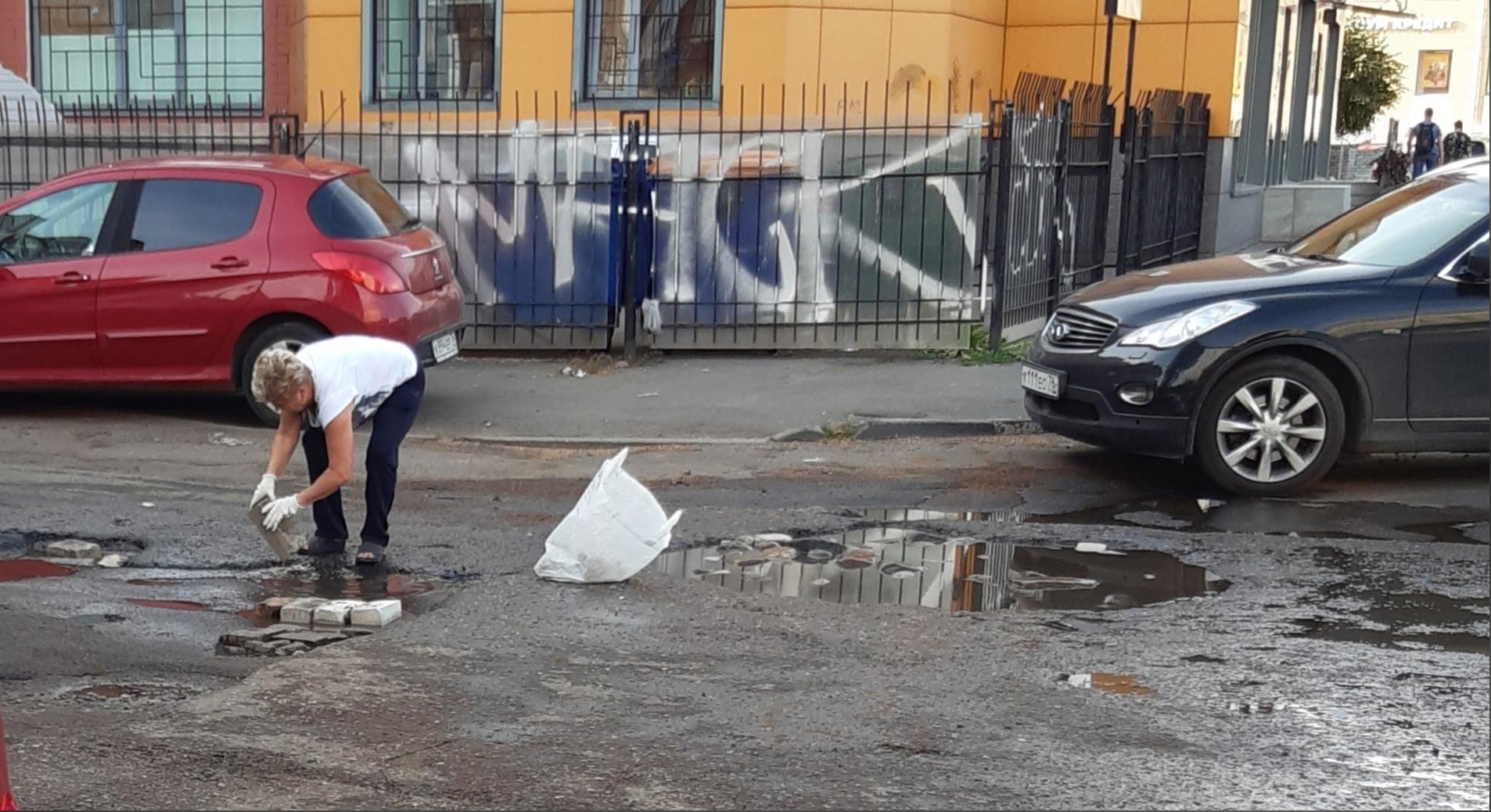 В Ярославле женщина с пакетом кирпичей заделала яму на дороге у ТЮЗа